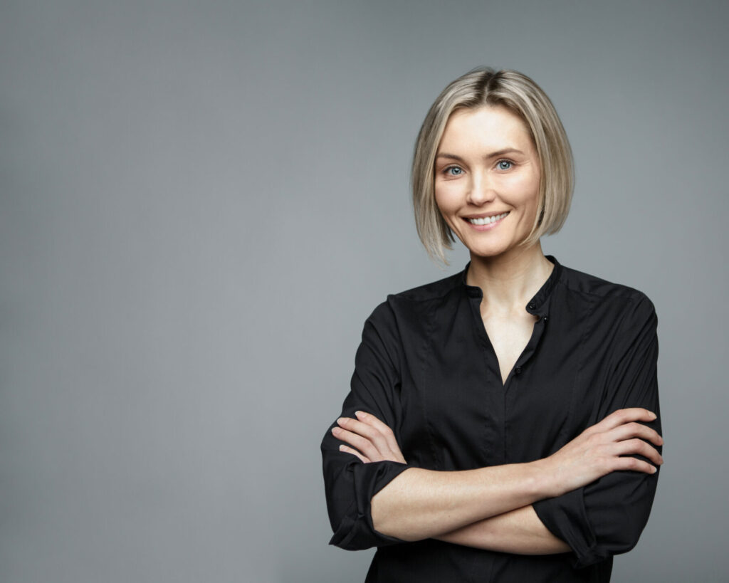 Beautiful middle-aged woman on a gray background in a black blouse smiling. Successful and confident businesswoman. Beautiful and healthy teeth. Natural beauty.